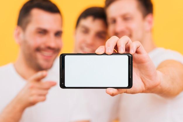 Defocused amigo masculino tres mostrando teléfono inteligente con pantalla en blanco