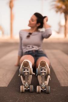 Defocused joven mujer patinadora sentada en el camino con patines en sus piernas
