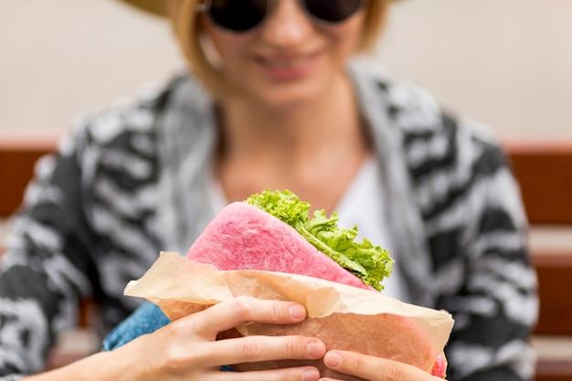 Defocused mujer sosteniendo un sandwich
