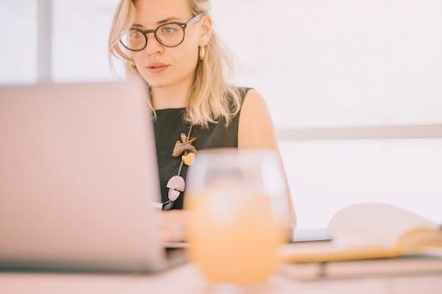 Defocused vaso de jugo frente a empresaria usando laptop