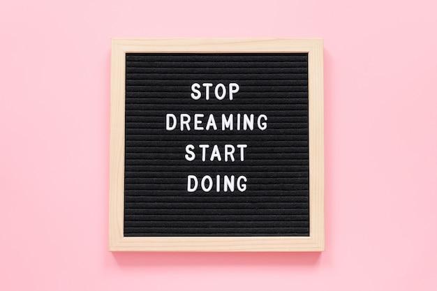 Deja de soñar comienza a hacer. cita motivacional en el pizarrón sobre fondo rosa. concepto inspiracional