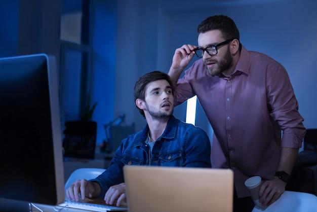 Déjame ver. buen hombre barbudo inteligente de pie detrás de su colega y arreglando sus gafas mientras mira la pantalla de la computadora