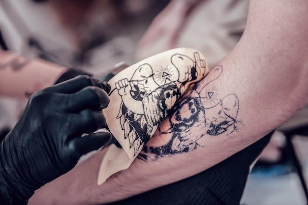 Dejando foto. cliente masculino preparándose para el procedimiento de tatuaje y maestro dejando una imagen temporal en su mano inferior