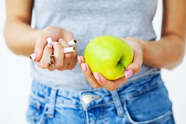 Dejar de fumar, cerca de mujer sosteniendo cigarrillos rotos y manzana verde