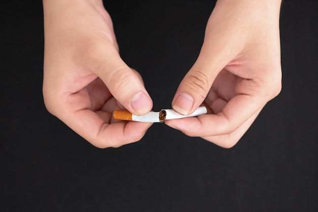 Dejar de fumar, mano sostener cigarrillo destruir aislado en negro