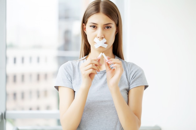 Deje de fumar, una mujer joven con la boca sellada llama la atención sobre los efectos nocivos del tabaco en la salud