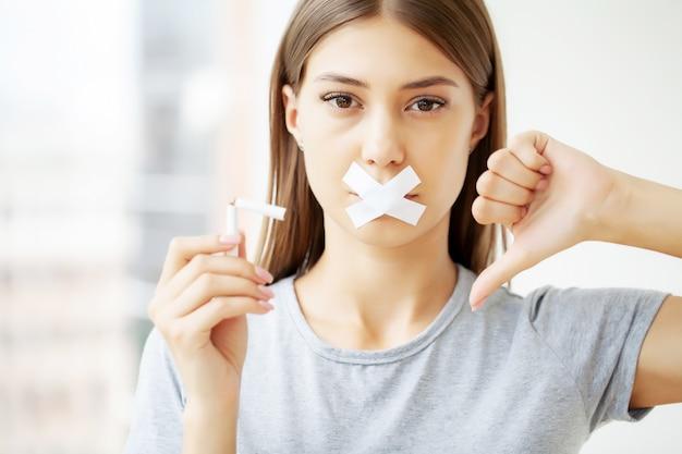 Deje de fumar, una mujer joven rompe un cigarrillo instando a dejar de fumar