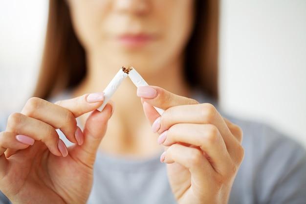 Deje de fumar, mujer sosteniendo un cigarrillo roto.