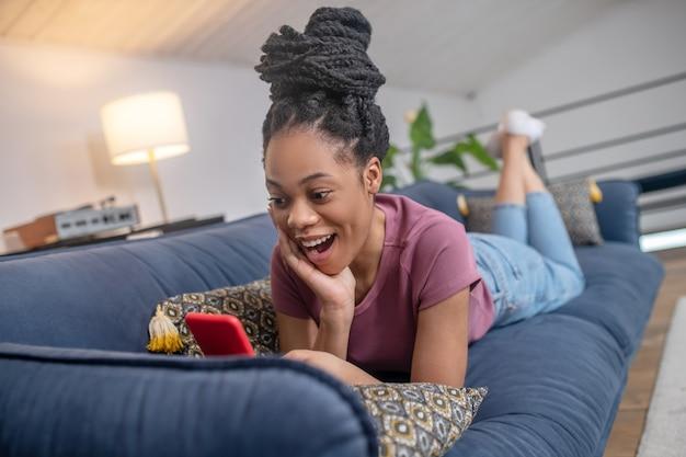 Deleite, emoción. entusiasta sorprendida joven afroamericana con cabello negro mirando smartphone acostado en el sofá en casa