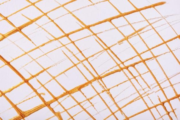 Delgadas líneas doradas y salpicaduras dibujadas sobre fondo blanco. telón de fondo de arte abstracto con trazo decorativo de pincel amarillo. cuadro acrílico con raya de cuadrícula gráfica.