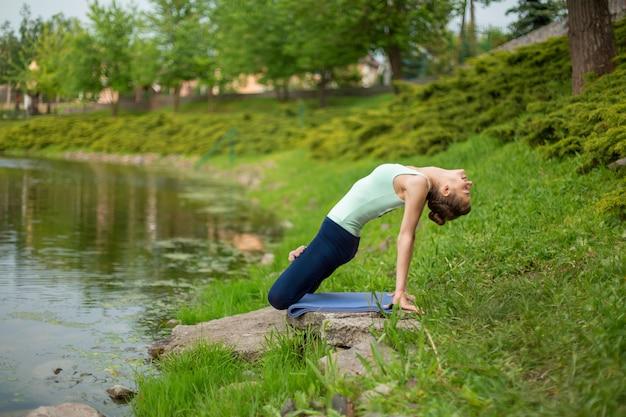 Delgado chica morena haciendo yoga en el verano en un césped verde