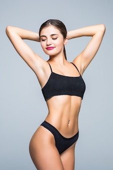 Delgado cuerpo de mujer joven en bikini negro. chica con figura deportiva saludable en la pared blanca