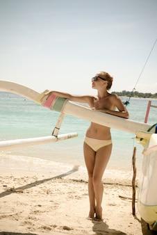 Delgado mujer joven en la playa tropical