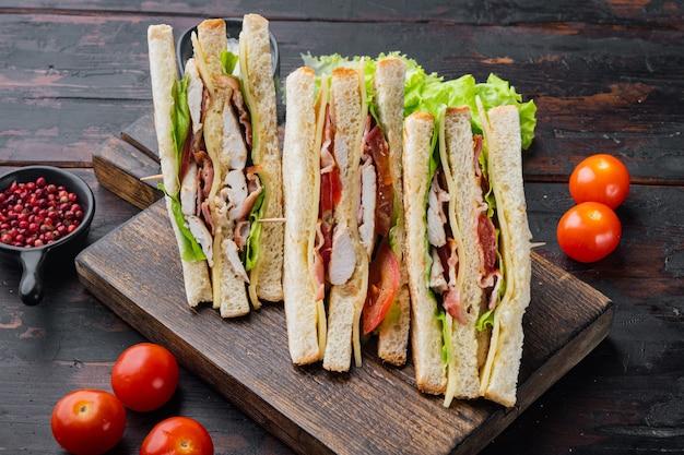 Deli sándwich fresco con pollo, sobre mesa de madera oscura.