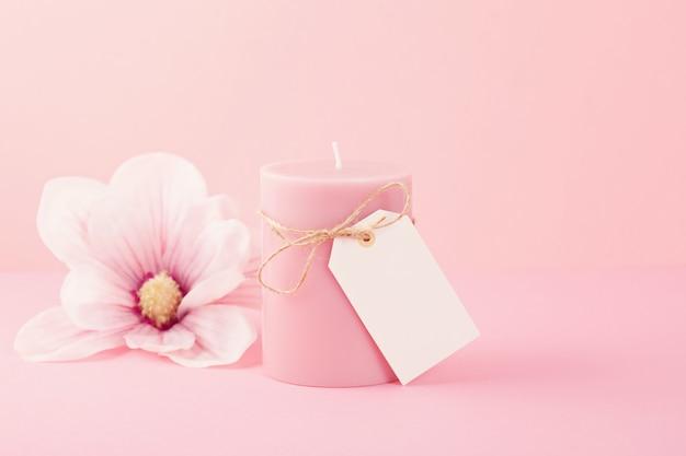 Delicada vela perfumada de flores sobre el fondo rosa pastel con espacio de copia