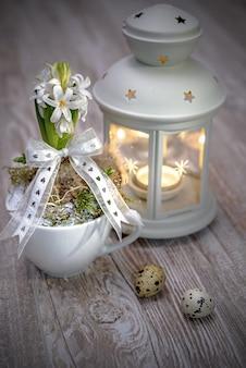 Delicado jacinto de perlas blancas con linterna blanca y huevos de codorniz sobre madera
