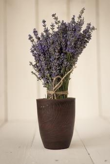 Delicado ramo púrpura de flores de lavanda en un vaso de madera vintage con olor a provenza francesa.