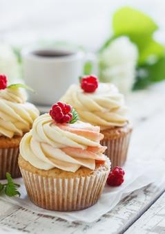 Delicados cupcakes de vainilla con crema y frambuesas sobre una madera blanca