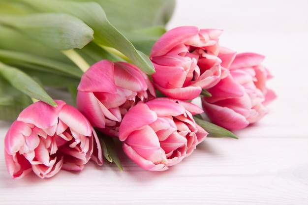 Delicados tulipanes de color rosa sobre un blanco de madera
