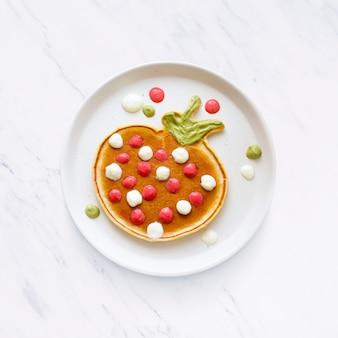 Delicia para el desayuno de panqueques para niños, con forma de fresa divertida
