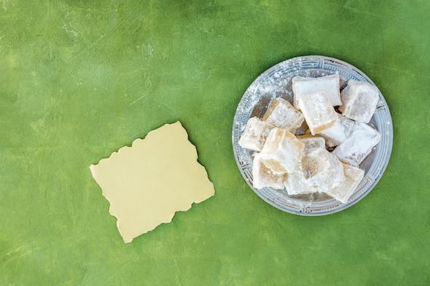 Delicia turca dulce en plato con papel pequeño.