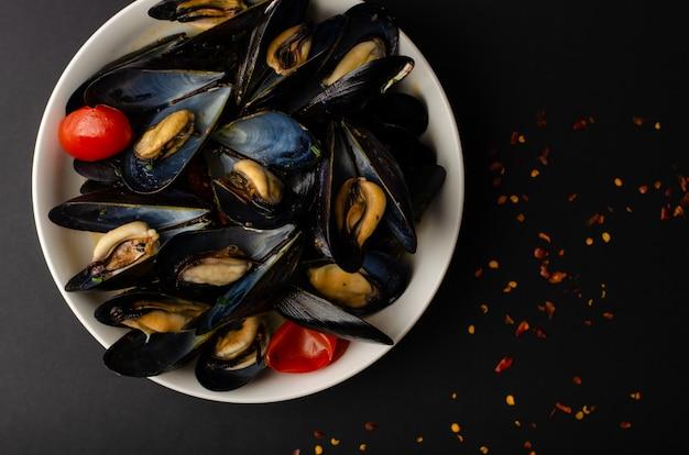 Delicias de mariscos italianos. sopa de mejillones al vapor en vino con tomates y pimientos picantes sobre fondo negro