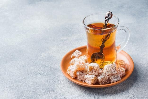 Delicias turcas con avellana en un recipiente de metal tallado y té en una taza de vidrio