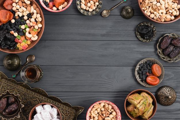 Delicias turcas lukum; baklava; frutos secos y nueces sobre fondo de madera con espacio en el centro para escribir el texto