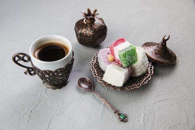 Delicias turcas con taza de café en mesa gris