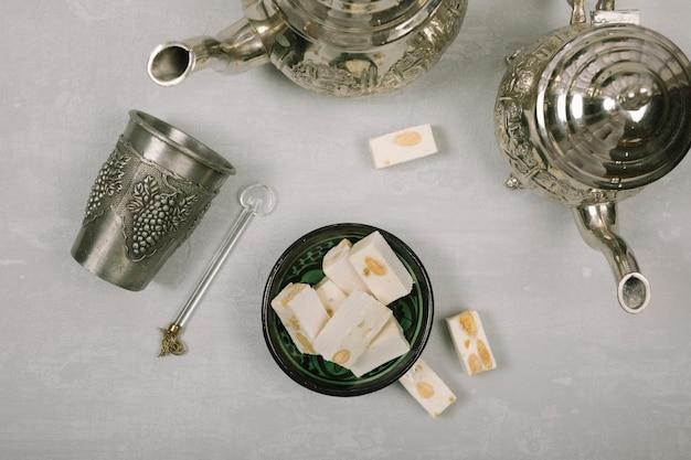 Delicias turcas con teteras en mesa blanca.