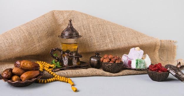 Delicias turcas con vaso de té y dátiles frutales.