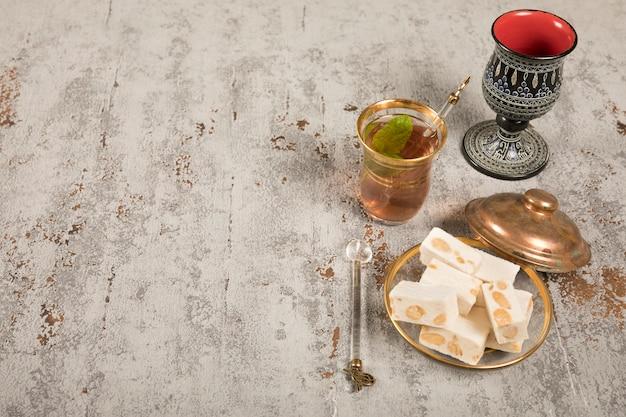 Delicias turcas con vaso de té en la mesa
