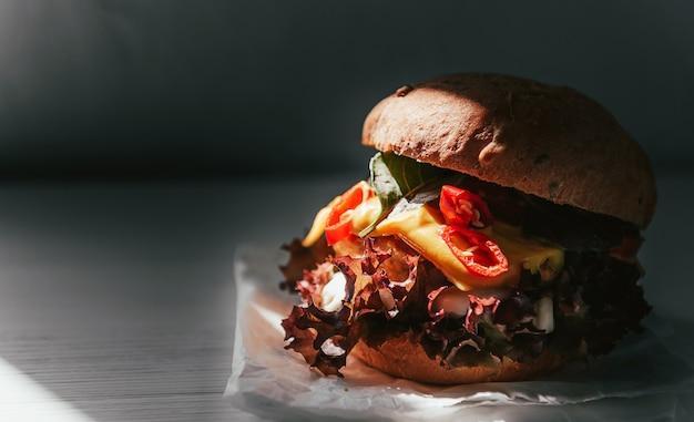 Deliciosa y apetitosa hamburguesa con chuleta de pollo, albahaca y ají sobre un fondo de madera blanca