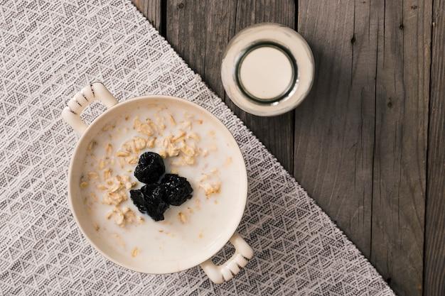 Deliciosa avena fresca nutritiva y saludable en mantel individual sobre la mesa de madera