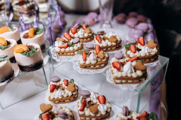 Deliciosa barra de caramelo con postres de mousse y galletas en forma de corazones