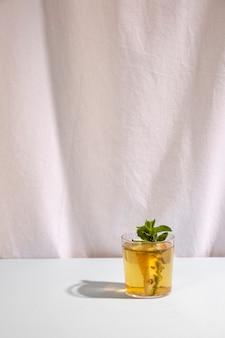 Deliciosa bebida fresca con una hoja de menta contra la cortina blanca