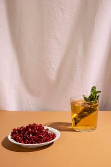 Deliciosa bebida con semillas de granada delante de la cortina blanca