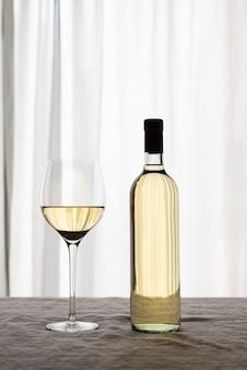 Deliciosa botella blanca de vino y vidrio.