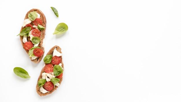Deliciosa bruschetta con hojas de albahaca aisladas en superficie blanca