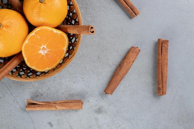 Deliciosa canasta de naranjas con cortes de canela sobre superficie de mármol