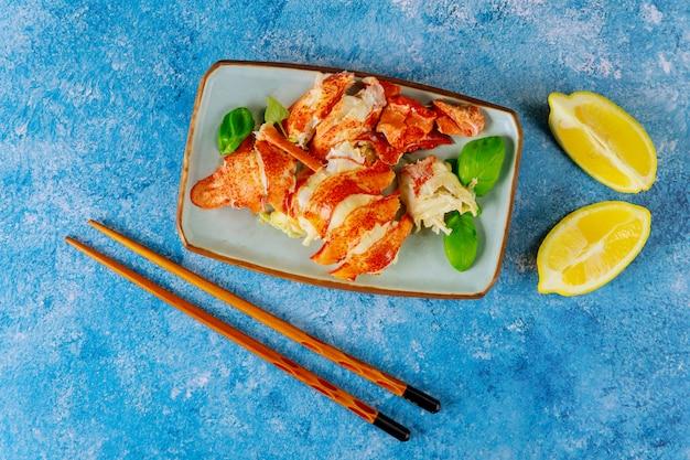 Deliciosa carne de langosta cocida en un tazón con limón en la cena