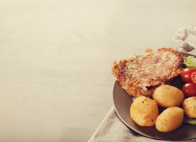 Deliciosa cena con filetes, papas hervidas y ensalada.