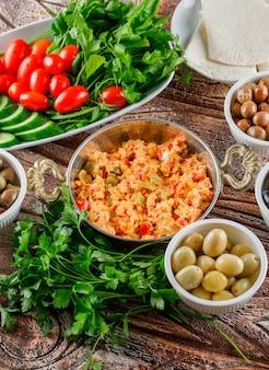 Deliciosa comida en una olla con ensalada, encurtidos en tazones vista de ángulo alto sobre una superficie de madera vertical