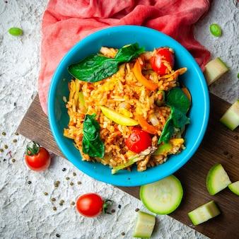 Deliciosa comida en un plato azul sobre un fondo de madera, tela roja y blanco con textura. vista superior.