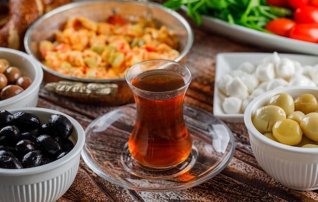 Deliciosa comida en un plato con una taza de té, ensalada, encurtidos vista superior sobre una superficie de madera
