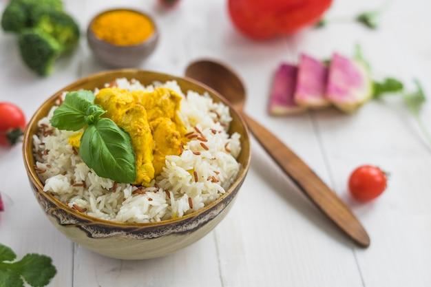 Deliciosa comida con pollo en un tazón cerca de la cuchara y los ingredientes en la mesa blanca