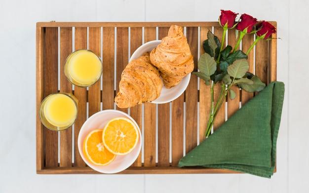 Deliciosa comida y rosas en la mesa del desayuno.