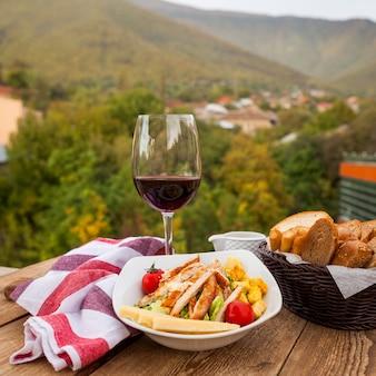 Deliciosa comida en un tazón con vino y pan vista lateral con un pueblo en el fondo