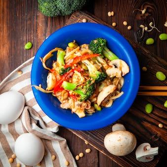 Deliciosa comida en una vista superior de la placa azul sobre un fondo de madera, tela y madera oscura