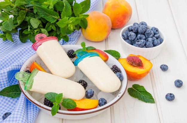Deliciosa dieta sorbete de yogur con puré de durazno en un palo sobre un fondo blanco de madera